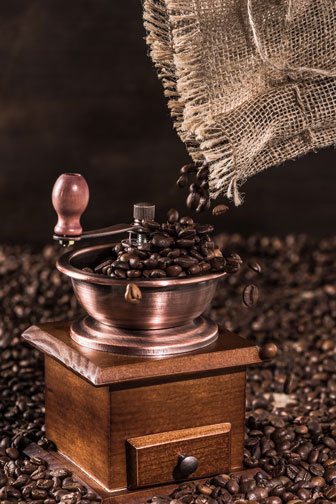 pouring coffee beans into a coffee mill